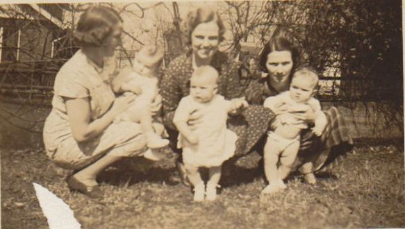 Aunt Hazel with Jimmy, Mother with me, Aunt Louise with Marjorie, in front of the grape arbor.