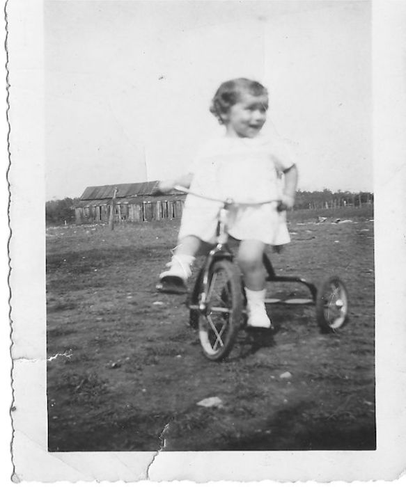 The oldest of the second cousins is Dorothy Jeane, here shown riding a tricycle on the farm.